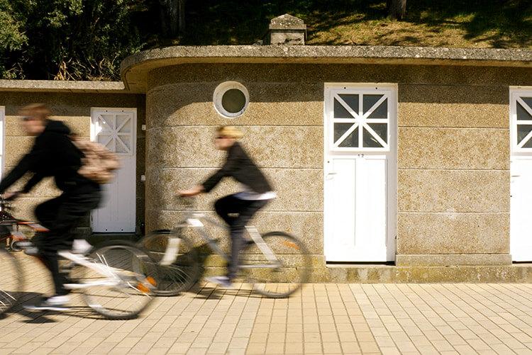 Où vont ces cyclistes qui passent devant les cabines de plages ?