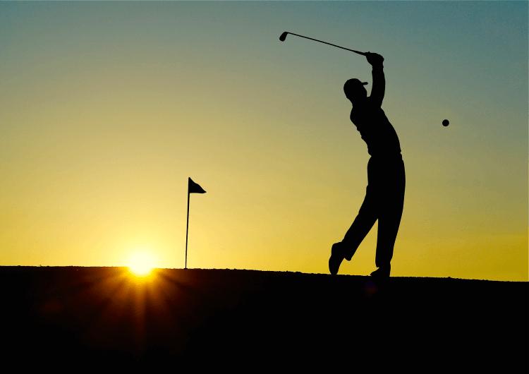 Joueur de golf au soleil couchant