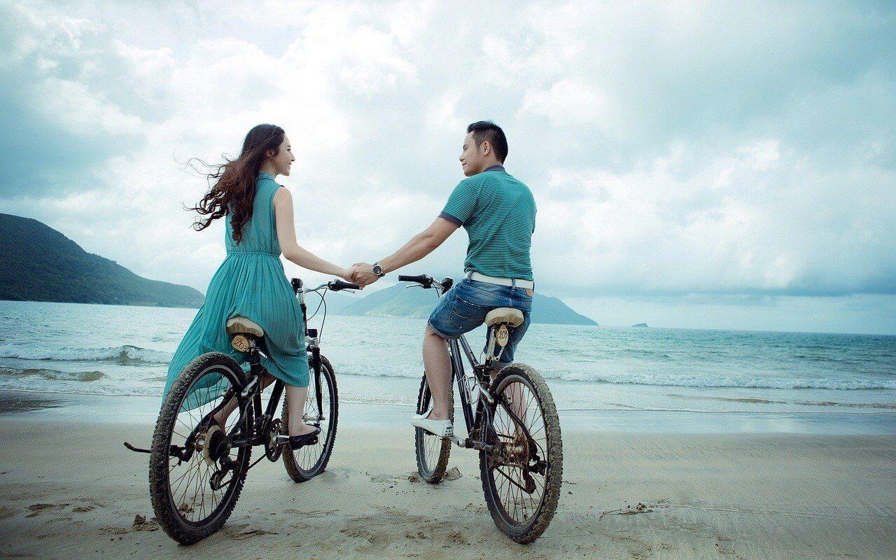 couple promenade a velo main vacances en resort au maroc